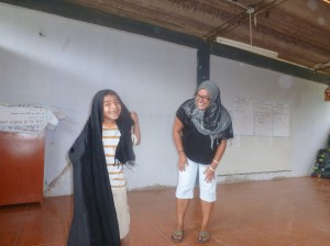 tina teaching eduardo the steps to wrapping the hijab.